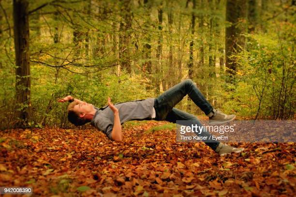 Man Levitating Over Autumn Leaves In Forest