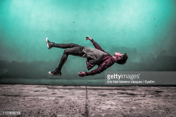 man levitating over footpath by wall - in de lucht zwevend stockfoto's en -beelden