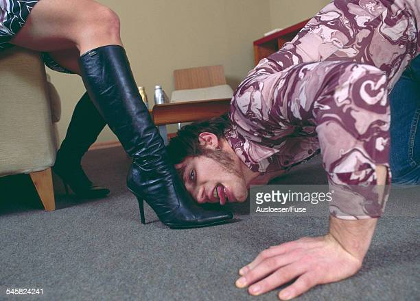 man licking the boots of a woman - foot fetishes stock pictures, royalty-free photos & images