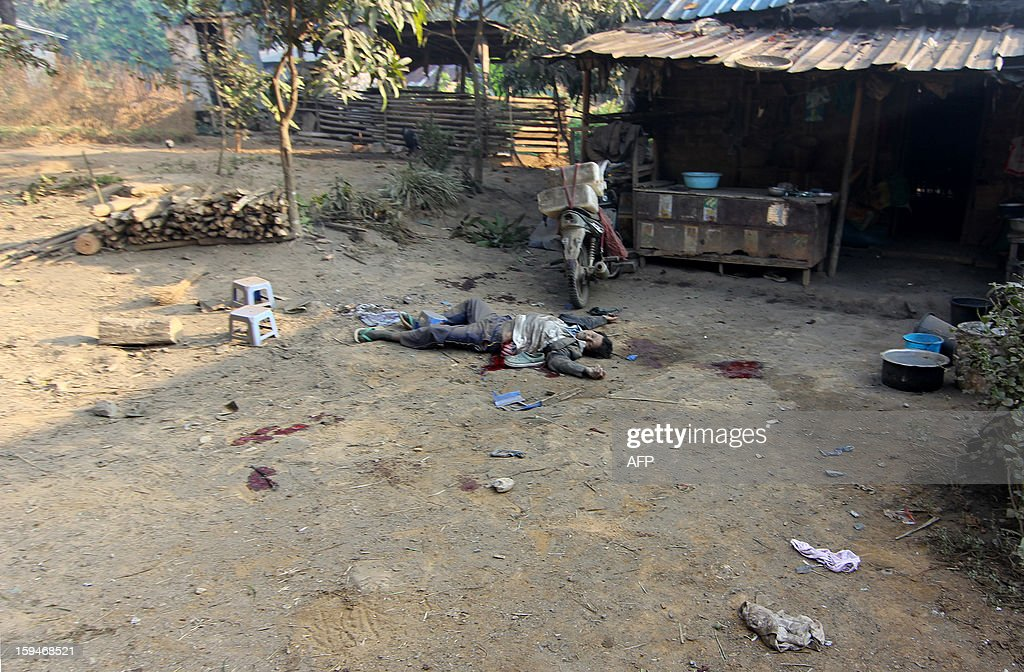 A man lies dead from artillery fire, in Laiza on January 14, 2013. Kachin rebels said three civilians were killed and six wounded in the first attack by Myanmar forces on their northern stronghold, as fighting escalates in the country's last active civil war. AFP PHOTO/ Tony NEIL