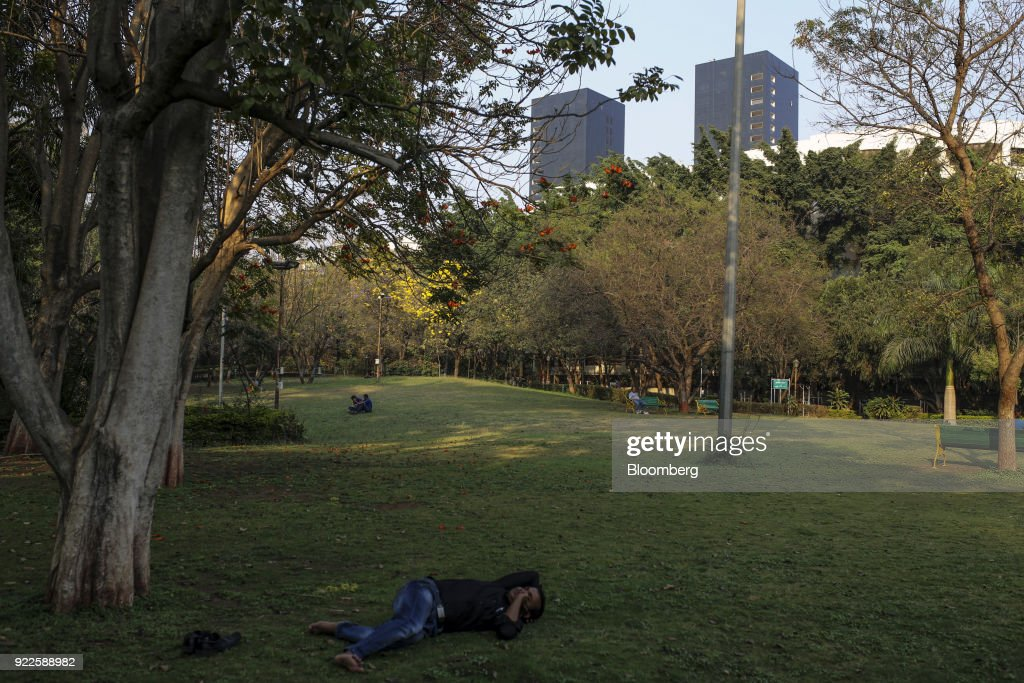 A man lies in a park as the Trump Towers Pune complex, developed by Panchshil Corp Park Pvt., stands in the distance in Pune, Maharashtra, India, on Wednesday, Feb. 21, 2018. Donald Trump Jr. is slated to speak on foreign policy at an event in New Delhi where Indian Prime MinisterNarendra Modiis also scheduled to speak. Photographer: Dhiraj Singh/Bloomberg via Getty Images