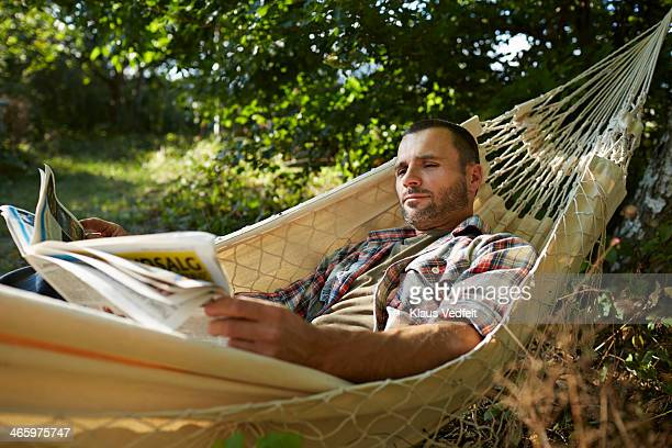 Man lies in hammock reading the paper