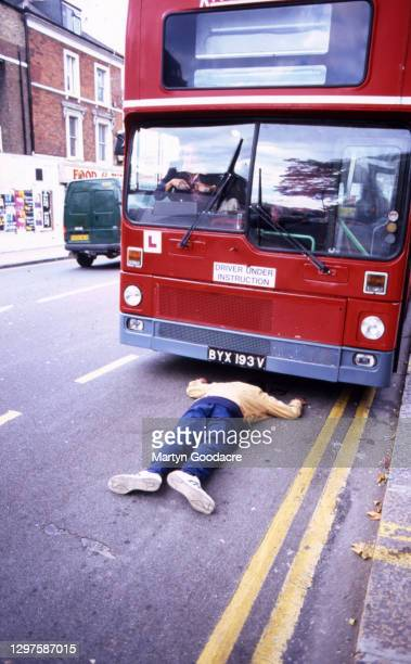 Man lies in the street in front of a double decker bus with Pop Will Eat Itself drummer Fuzz Townshend at the wheel, in a humorous simulation of a...