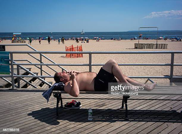 A man lies on a bench along the boardwalk July 24 2015 at Coney Island Beach in the Brooklyn borough of New York