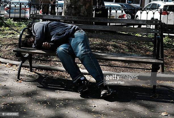 A man lies on a bench in a neighborhood park with a high rate of poverty and illegal drug use on October 14 2016 in New York City Staten Island a New...