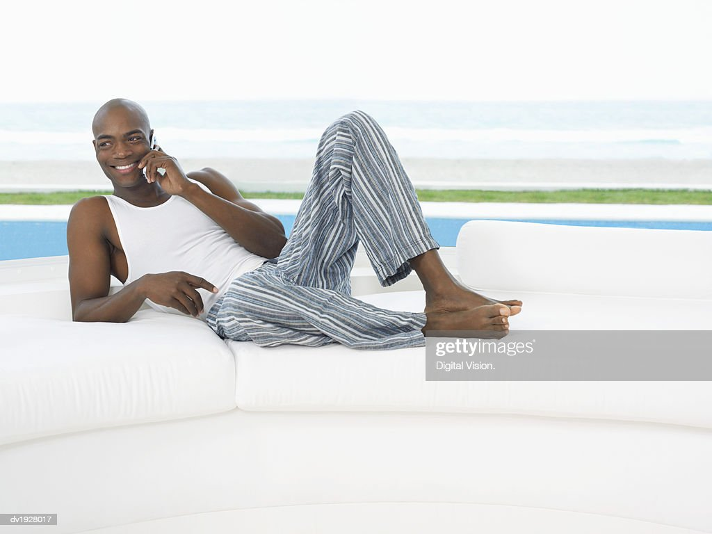 Man Lies on a Sofa by a Pool Talking on His Mobile Phone : Stock Photo