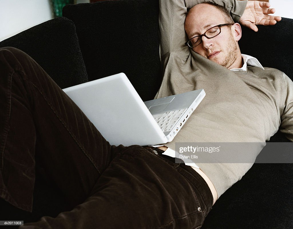 Man Lies on a Sofa, Sleeping, a Laptop on His Lap : Stock Photo