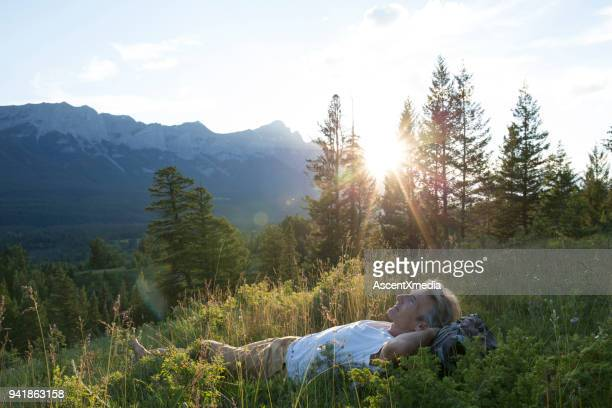 man lies on back in mountain meadow - lying down foto e immagini stock