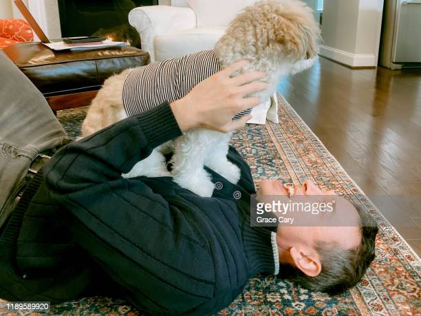man lies on floor with dog on chest - hairy man chest stock photos and pictures