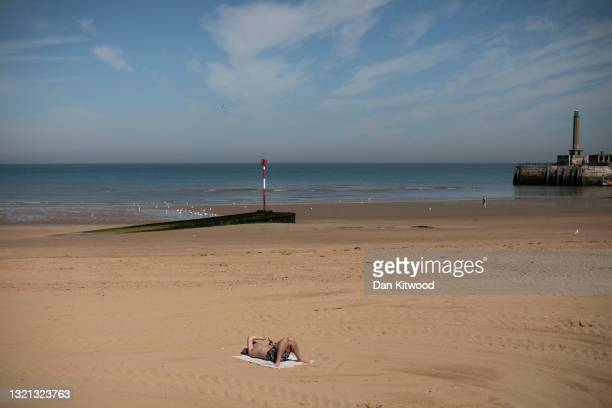 Man lies on the beach in the early morning sunshine on June 02, 2021 in Margate, England. The start of meteorological summer was met with high...
