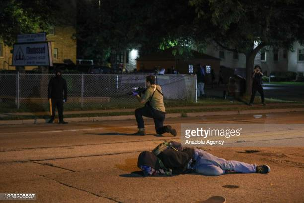 Man lies on the ground after being shot in the chest by armed civilian Kyle Rittenhouse during confrontations between protesters and armed civilians,...