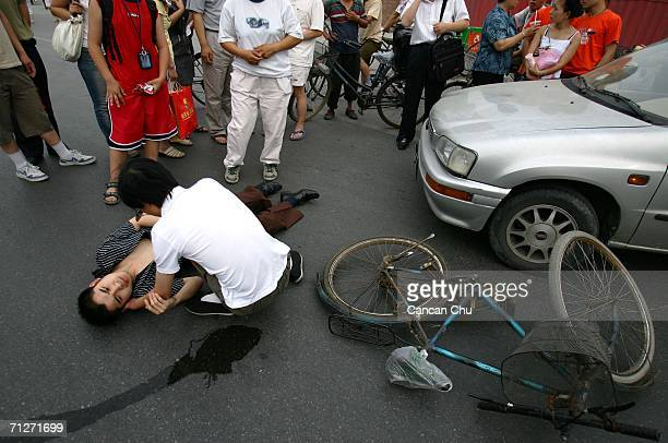 A man lies on the ground after his bicycle was hit by a car during a traffic accident on June 22 2006 in Beijing China According to state media China...