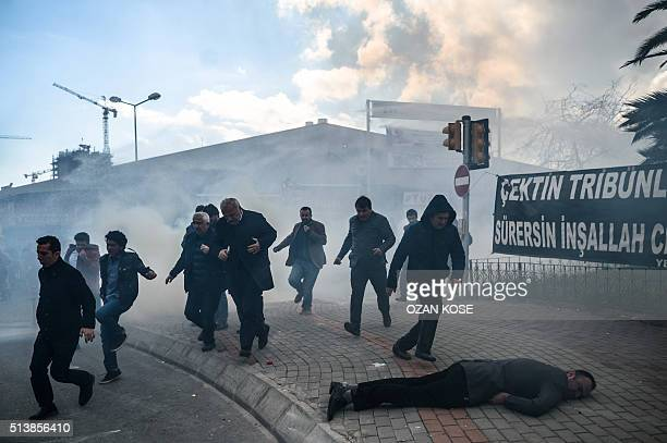 TOPSHOT A man lies on the ground as others run as Turkish antiriot police officers use tear gas to disperse supporters in front of the headquarters...