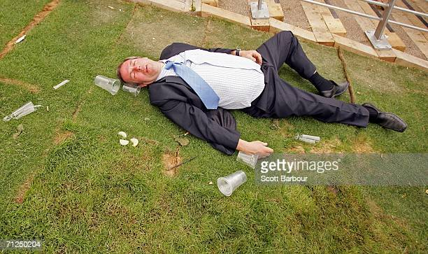 A man lies on the ground as racegoers walk past him on the first day of Royal Ascot at the Ascot Racecourse on June 20 2006 in Ascot England The...