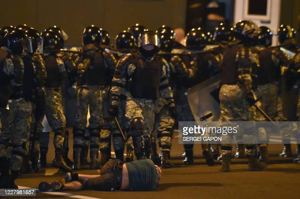 A man lies on the ground in front of riot police during a protest after polls closed in Belarus' presidential election in Minsk on August 9 2020