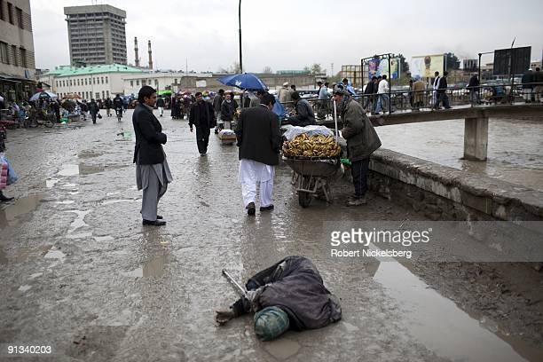A man lies on the road begging April 6 2009 near the downtown Kabul Afghanistan money market Kabul has an estimated population of 35 4 million people