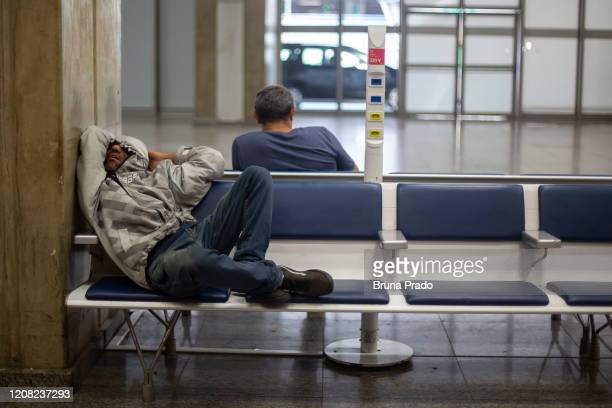 A man lies on the seats at the Tom Jobim International Airport on March 25 2020 in Rio de Janeiro Brazil The federal government have imposed an entry...