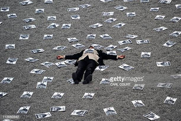 A man lies on the Sunflower Seeds installation by Chinese artist Ai Wewei at the Tate Modern in central London on April 9 after taking part in a...