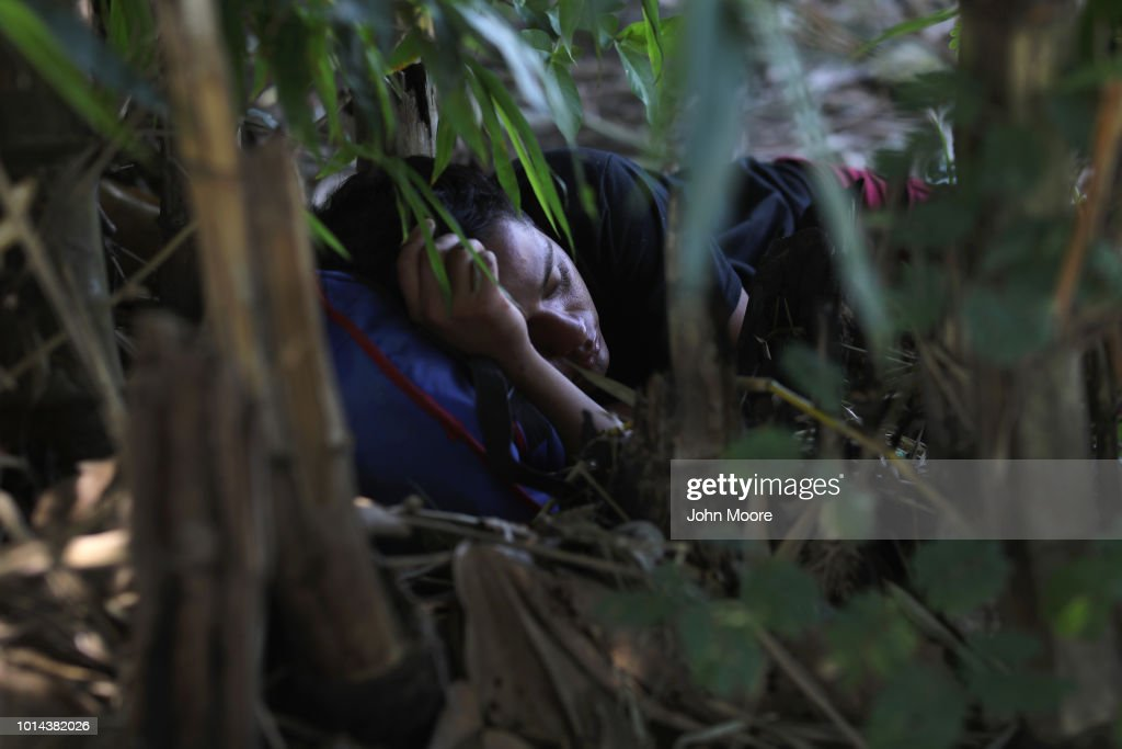 A man lies sleeping along the Suchiate River which forms the border between Guatemala and Mexico on August 9, 2018 in Tecum Uman, Guatemala. Rafts tranport people and contraband across the river at an illegal crossing point located near the international bridge connecting the two countries, circumventing immigration and customs checkpoints.