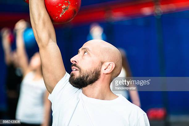 man lifting a kettlebell - skinny man fat woman stock pictures, royalty-free photos & images