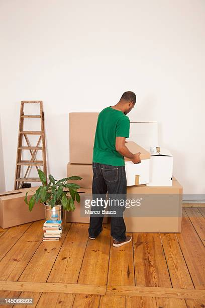 A man lifting a moving box to put it on top of other boxes