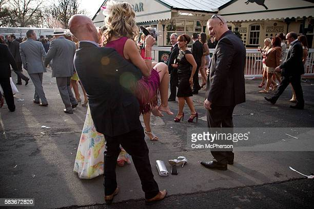 A man lifting a woman off the ground as they are making her way towards the exit at Aintree after the second day of the annual Grand National meeting...