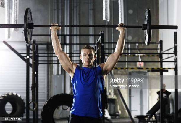 man lifting barbell above his head - barbell stock pictures, royalty-free photos & images