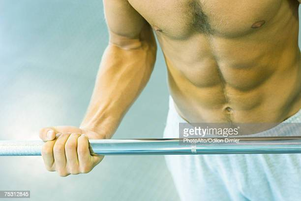 Man lifting barbell, close-up of mid section