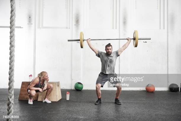 man lifting barbell in cross training gym - sollevare foto e immagini stock