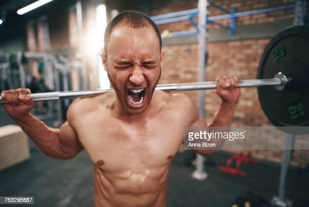 Man lifting barbell in health club. Mielec, Poland