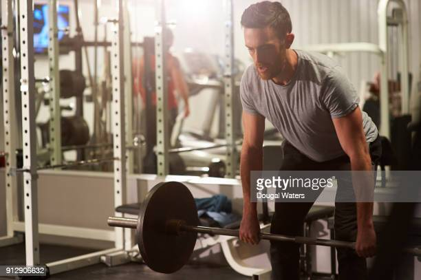 man lifting barbell weights at the gym. - 練習 ストックフォトと画像