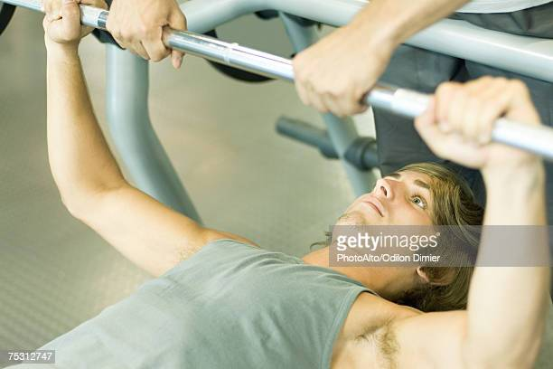 man lifting barbell while second man spots - lying on back stock pictures, royalty-free photos & images