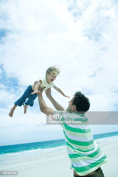 Man lifting child into air on beach