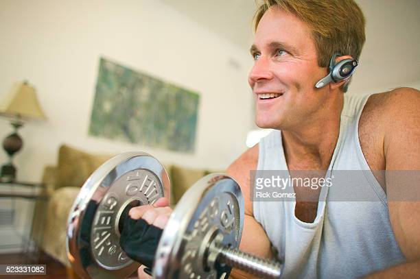 man lifting dumbbell and talking on cell phone headset - mid adult men stock pictures, royalty-free photos & images