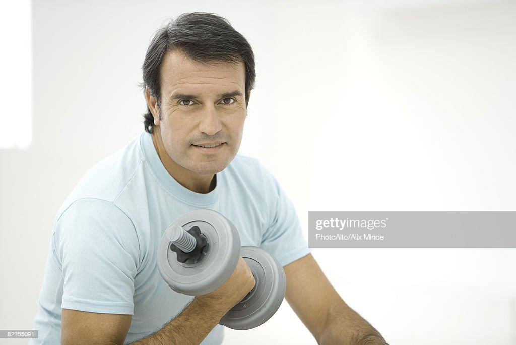Man lifting dumbbell, looking at camera : Stock Photo