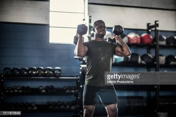man lifting dumbells at cross training gym - dumbbell stock pictures, royalty-free photos & images