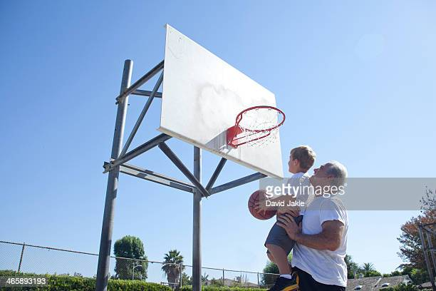 Man lifting grandson to basketball hoop