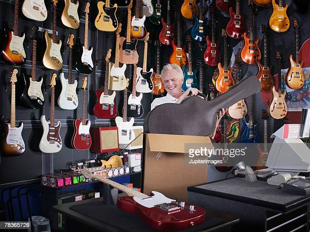 Man lifting guitar case out of box