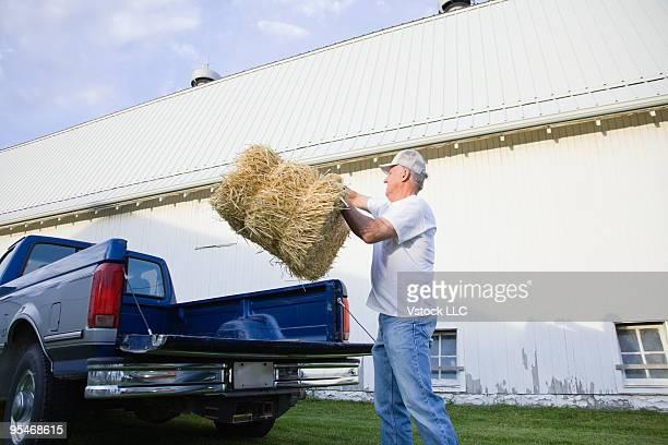 Man lifting hay bales
