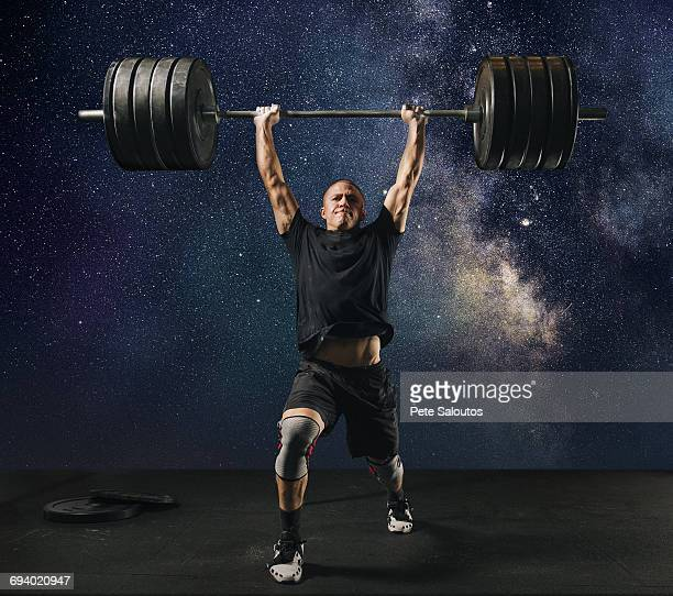 man lifting heavy barbell against starry sky - weight training stock pictures, royalty-free photos & images