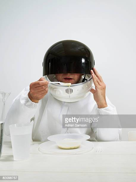 Man lifting helmet to eat