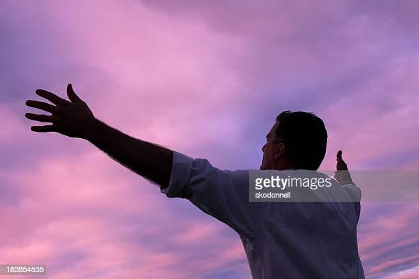 man lifting his hands to the sky - christianity stock pictures, royalty-free photos & images