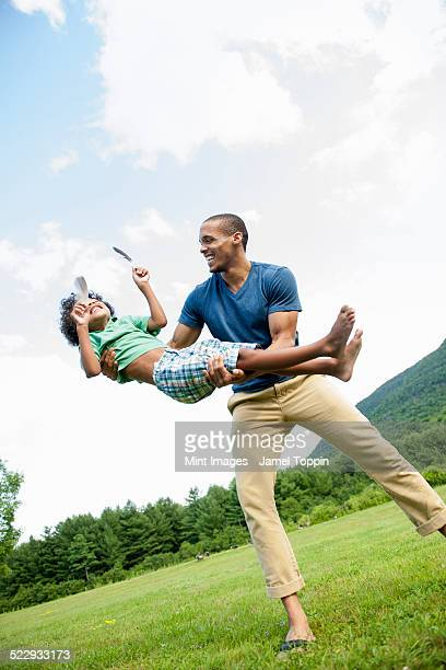 a man lifting his son up in his arms, playing outdoors. - mixed wrestling stockfoto's en -beelden