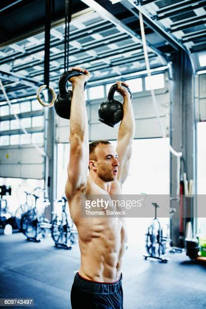 Man lifting kettlebells above head during workout