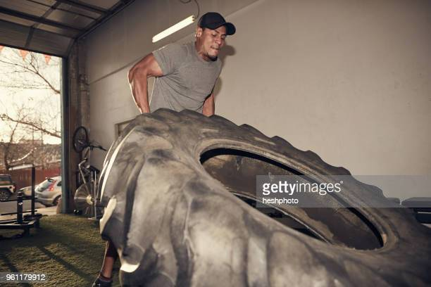 man lifting large tire - heshphoto stock pictures, royalty-free photos & images