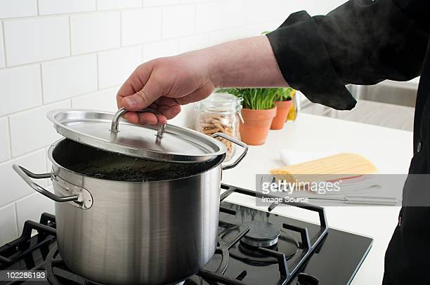 man lifting lid on saucepan - lid stock photos and pictures