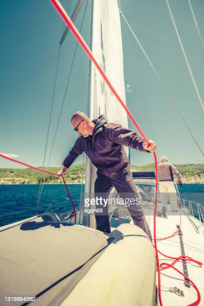 man lifting the sail - sailor suit stock pictures, royalty-free photos & images