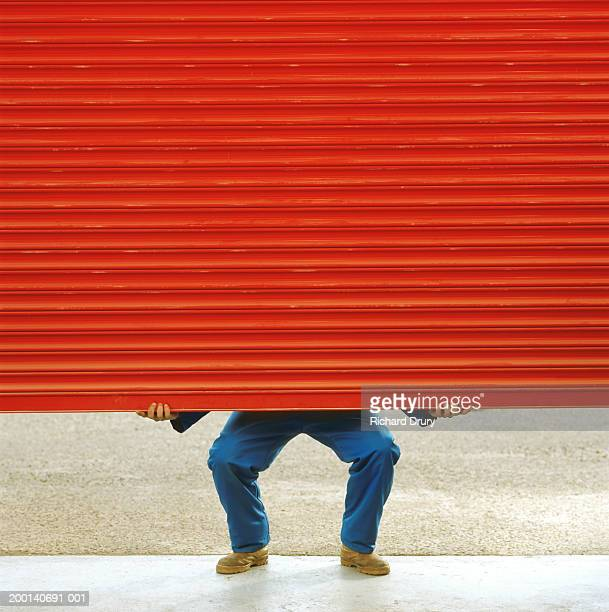 man lifting warehouse door, low section - industrial door stock pictures, royalty-free photos & images