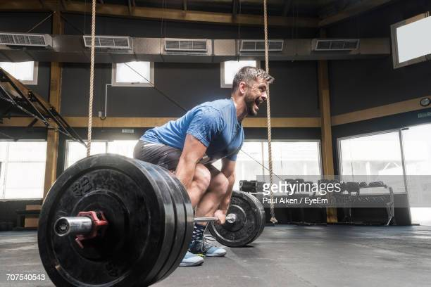 man lifting weights at gym - aikāne stock pictures, royalty-free photos & images