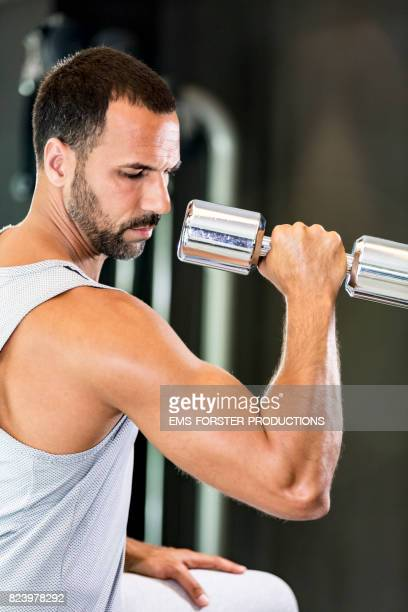 man lifting weights in gym on a bench - ems forster productions stock pictures, royalty-free photos & images